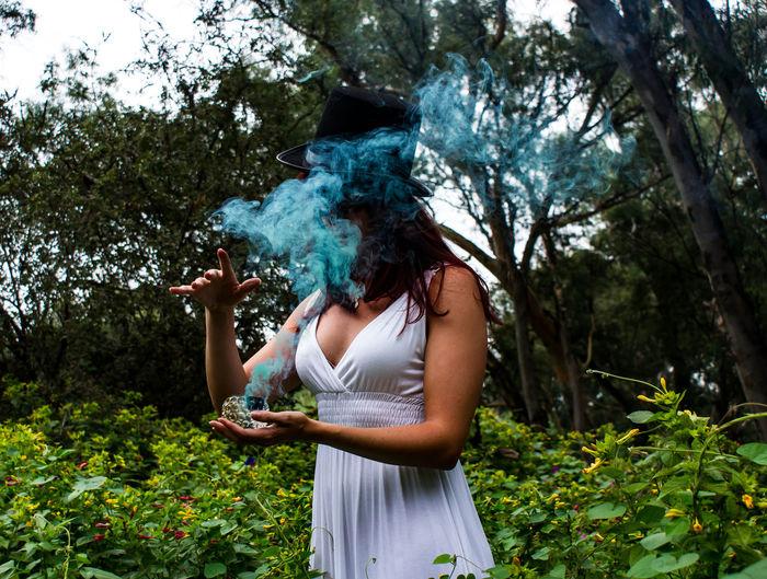 Woman stirring up blue smoke in garden
