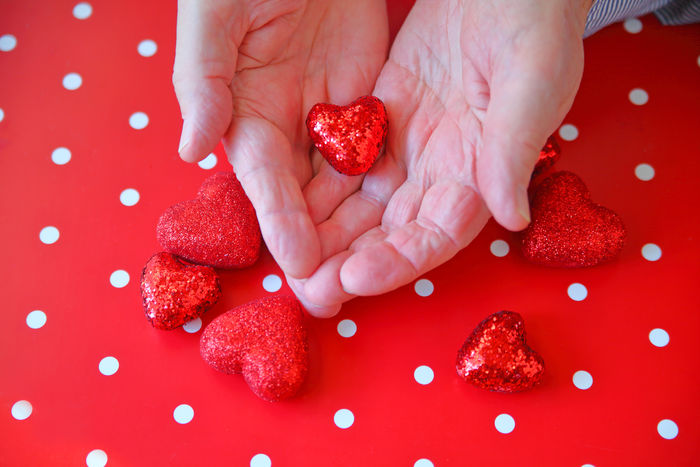 Man with shiny heart in hands over more hearts on polka dot background Fondness Hands Holiday Love Man Natural Light Polka Dots  Romantic Sentimental Shiny Valentine's Day  Affection Close-up Day Fingers Girly Glittery Holding Indoors  One Person People Red Red Hearts Studio Shot Symbols
