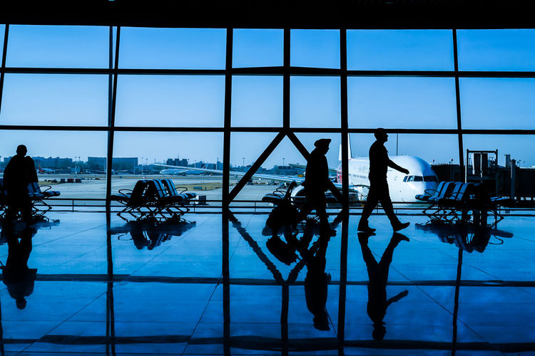 Silhouette people at airport against sky