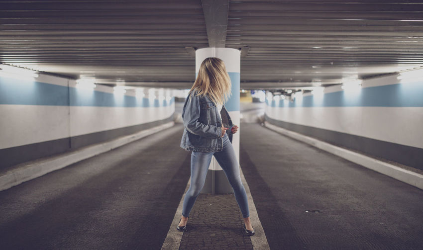 Woman standing in illuminated subway station