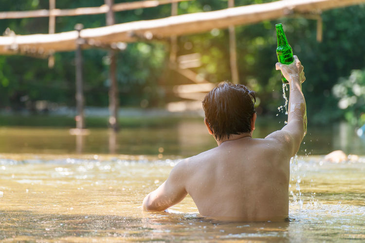 Water Rear View Real People One Person Lifestyles Leisure Activity Men Shirtless Focus On Foreground Nature Food And Drink Refreshment Day Vacations Waist Up Drink Lake Trip Outdoors Human Arm Arms Raised Drinking Swimming Pool