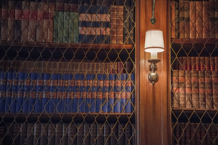 Illuminated Electric Lamp Mounted On Book Shelf In Library