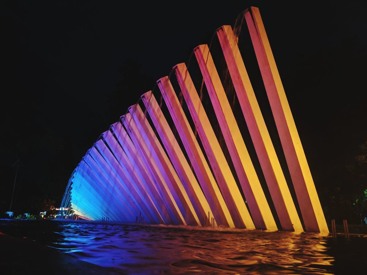 night, illuminated, water, multi colored, no people, nature, reflection, pattern, sea, glowing, motion, sky, architecture, built structure, outdoors, waterfront, striped, lighting equipment
