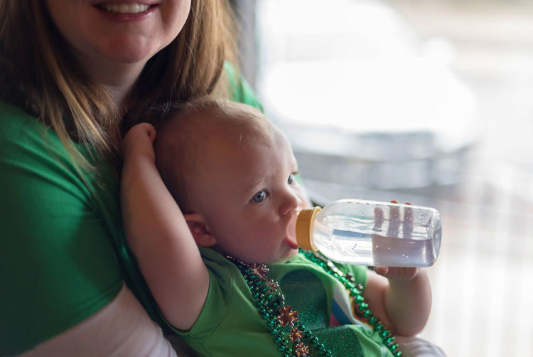 Midsection of woman carrying daughter drinking water from baby bottle