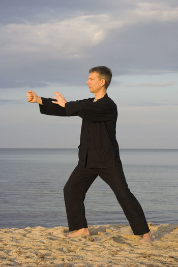 Man practicing martial arts at sandy beach against sky