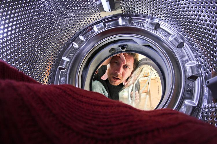 Portrait of man seen through washing machine