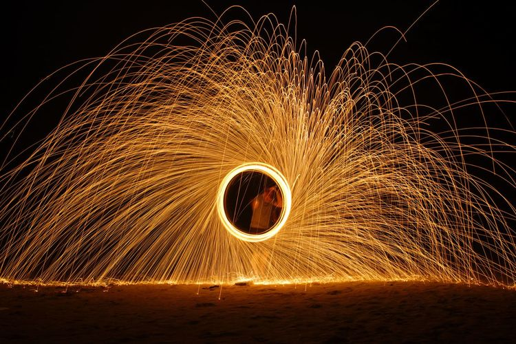 Man Standing By Wire Wool Against Sky At Night