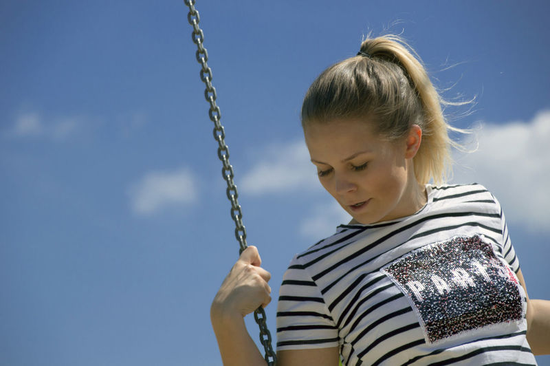 Low angle view of young woman looking down while swinging against sky