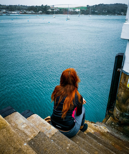 Rear view of woman looking at sea while sitting on staircase