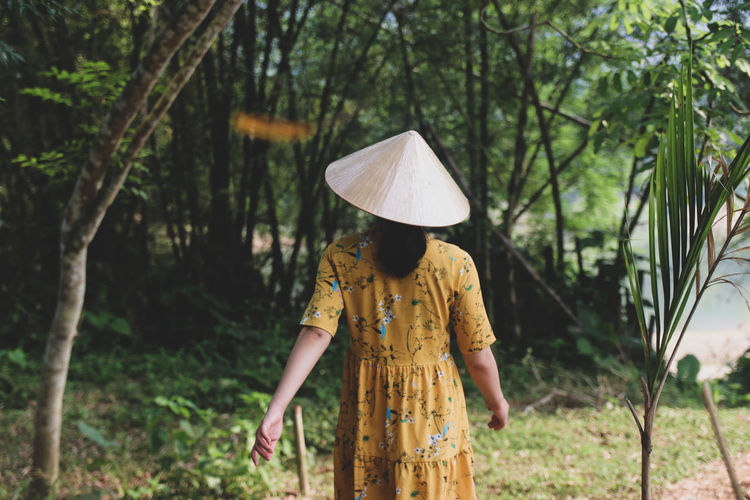 Rear view of woman wearing asian style conical hat walking in forest