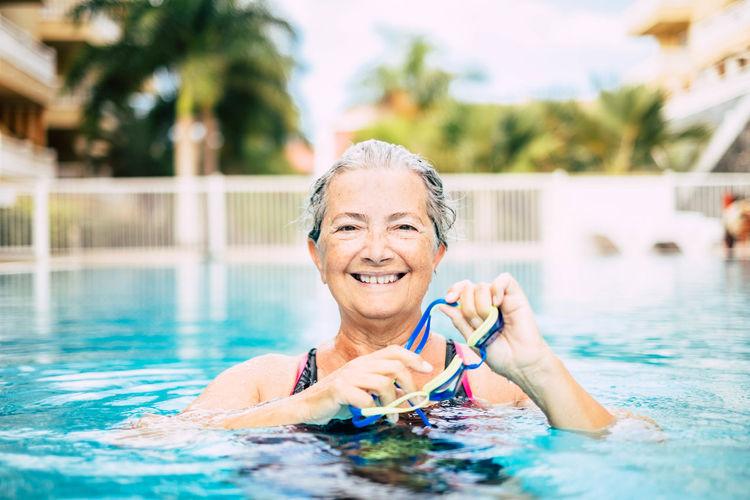 Portrait of smiling senior woman swimming in pool