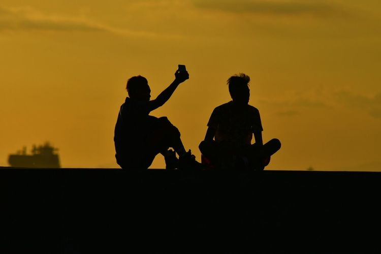 Silhouette man taking selfie with friend during sunset