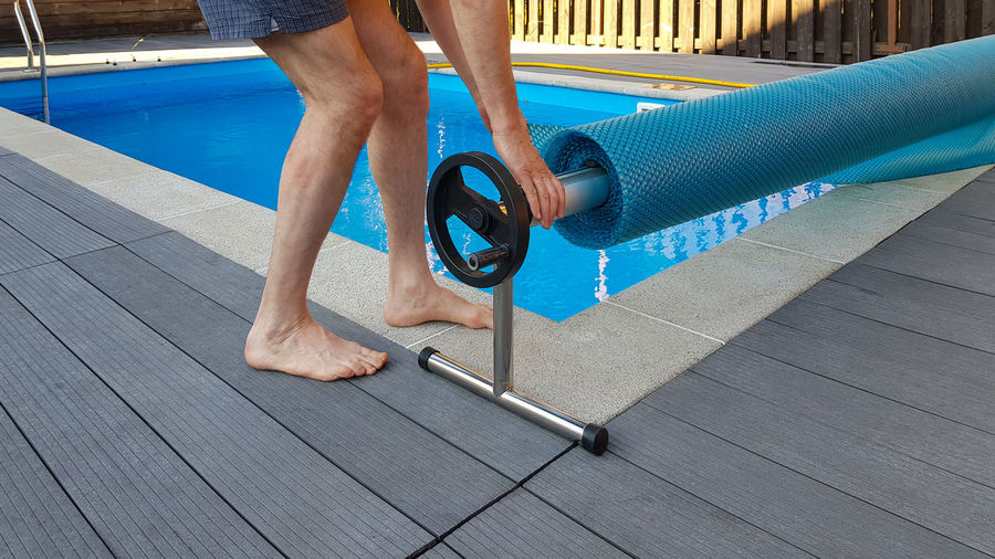 Low section of man standing on footpath by swimming pool