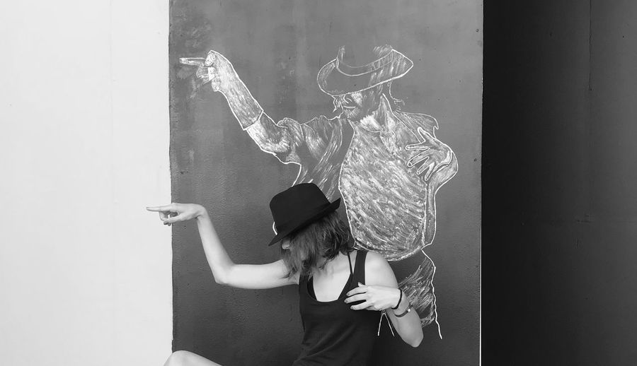 Young Woman Standing Against Drawing On Blackboard