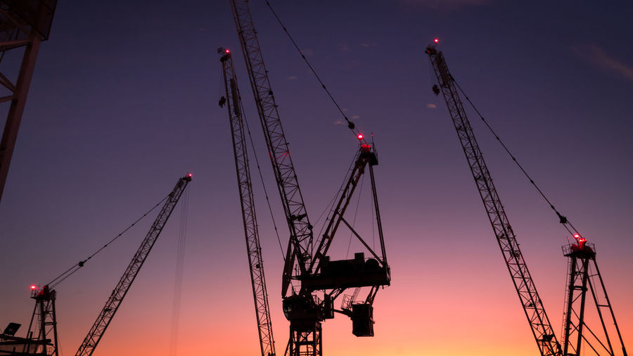 Low angle view of cranes against sky at sunset