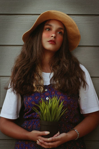 Plant Lady, 2018 Plant Beautiful Woman Beauty Casual Clothing Conceptual Photography  Contemplation Fashion Front View Hair Hairstyle Hat Leisure Activity Lifestyles Long Hair Looking At Camera One Person Plant Portrait Real People Standing Summer Teenager Waist Up Young Adult Young Women