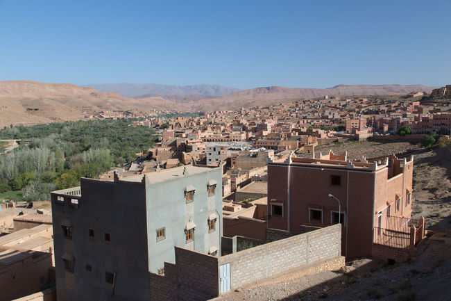 View of a town crossed by a river in Morocco, surounded by the desert and hills. Nobody Africa Architecture Blue Building Exterior Built Structure Cityscape Clear Sky Day Desert Deserts Around The World Hill Landscape Maroc Merzouga Morocco No People Ouarzazate Outdoors Residential Structure Sahara Sahara Desert Sky Town