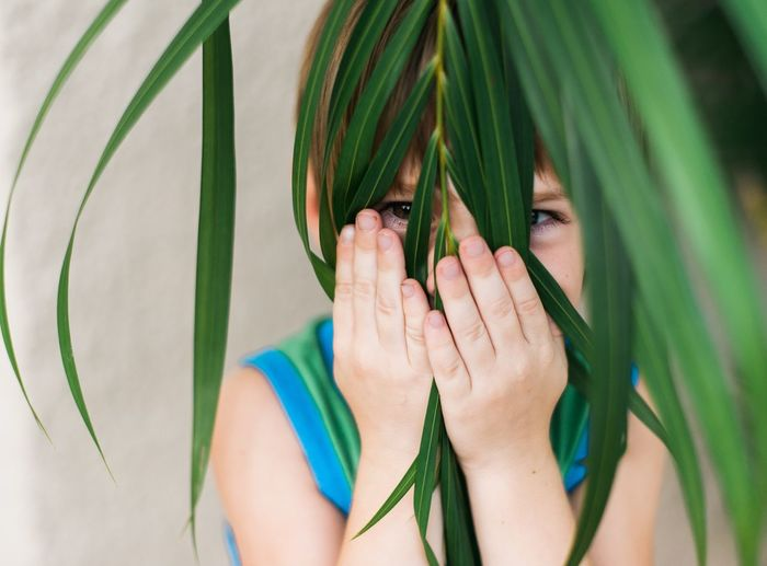 Childplay Pantone Colour Green Tropical Plant Cheeky Boy Eyes Are Soul Reflection Happy Kid Hiding From Mom Life Of A Mom Candid Photography From My Point Of View Eyeem Weekly Premium Collection Headshot Close-up Child Hands Children's Portraits Children Of The World