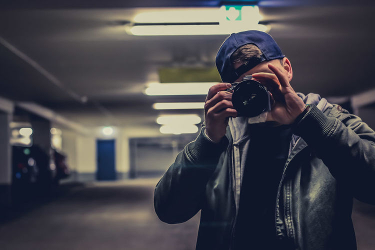 Man photographing while standing in parking lot
