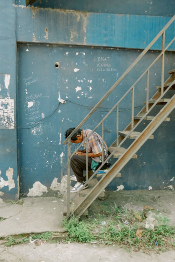 Man working on staircase against wall