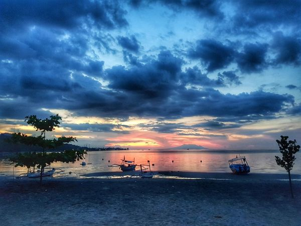 sunset at the beach in Bali Water Sea Sunset Beach Tree Multi Colored Sand Blue Nautical Vessel Beauty Romantic Sky Moody Sky Dramatic Sky Lightning Power In Nature Cloudscape Storm Cloud Salt Lake Low Tide Atmospheric Mood Seascape Jet Boat Summer Exploratorium