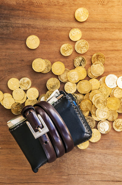 Top view of wallet tied with belt and gold coins on wooden tabletop Business Economy Wallet Bailout Banking Belt  Belt Tightening Coin Coins Concept Directly Above Earnings Expenses Finance Gold Coins Income Mortgage No People Savings Still Life Thrift Tied Top View