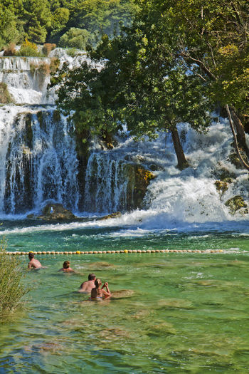 Tourists bath under the Krka waterfalls in Krka National park, great attraction near Sibenik. Krka river forms 17 waterfalls in an area of 400 m in length and 100 m in width. Bath Beautiful Nature Beauty In Nature Cascade Croatia Fun Krka National Park Krka Waterfall Lagoon Lake Leisure Nature Outdoors River Rocks And Water Scenery Sibenik Stream Summer Swimming The Great Outdoors - 2017 EyeEm Awards Tree Vacation Destination Water Waterscape