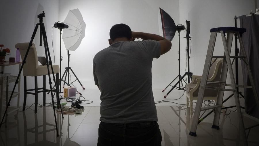Rear View Of Man Photographing In Studio