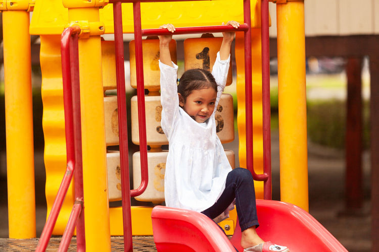 Thoughtful girl on slide at playground