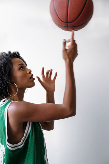 Portrait of a beautiful black women wearing basketball jersey holding basketball