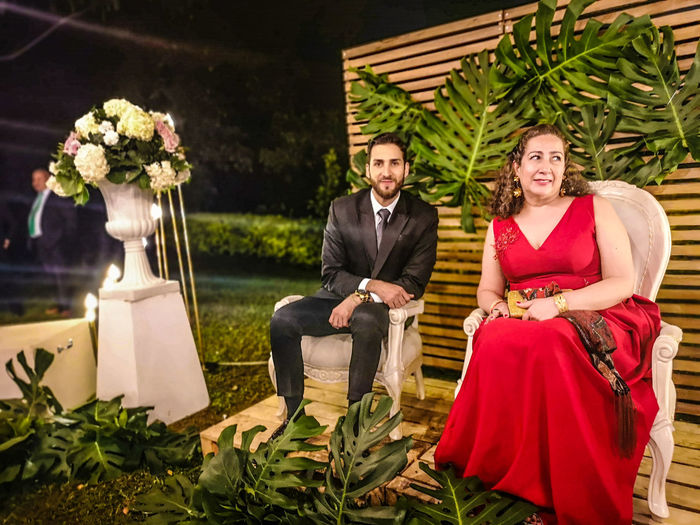 Portrait of smiling man by woman sitting on chair during wedding