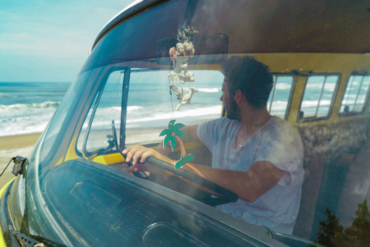 Man looking the waves form the yellow van. Surf Adult Adults Only Casual Clothing Day Leisure Activity Lifestyles Looking Through Window Men Nature One Man Only One Person Only Men Outdoors People Real People Sitting Surfing Transportation Truck Vacations Van Vanlife Waves Young Adult Fresh On Market 2018