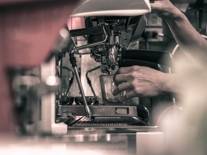 Cropped hands of barista making coffee in machinery
