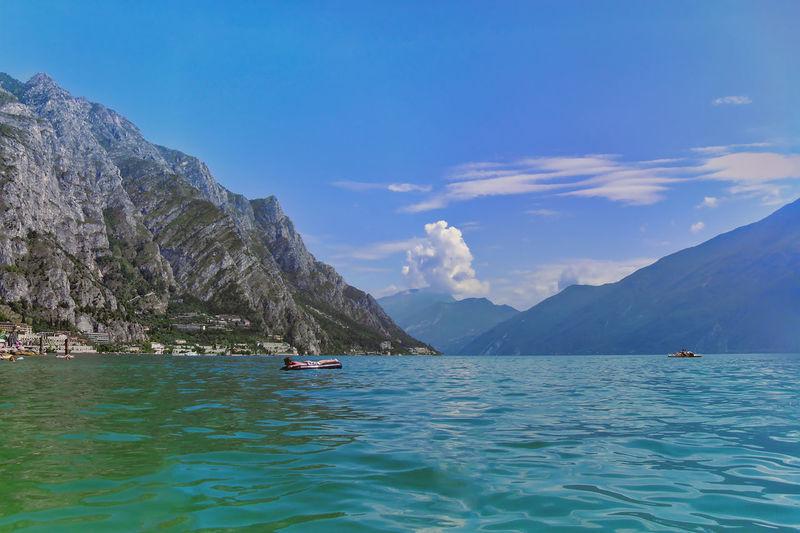 Teenage boy floating on lake against blue sky