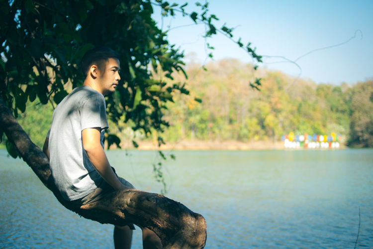 Thoughtful Young Man Sitting On Tree By Lake