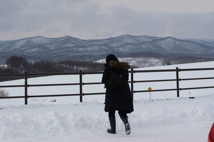 Rear view of woman walking on snow covered field against cloudy sky