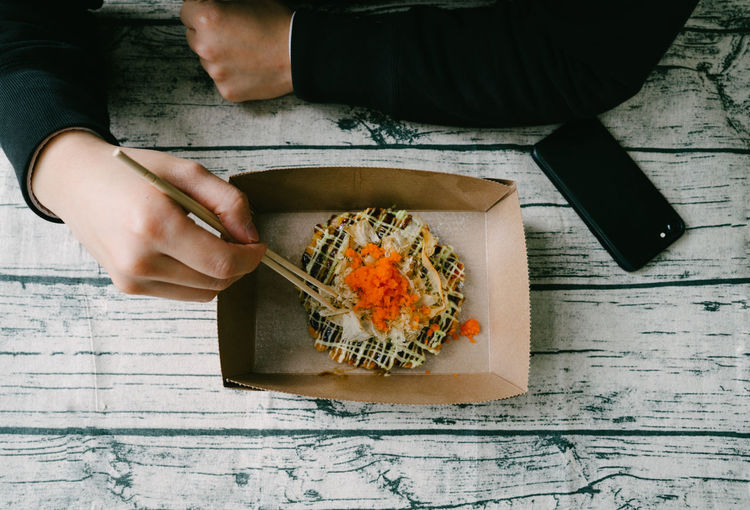 Eating Okonomiyaki on table Human Hand One Person Real People Hand Holding Food And Drink Food Lifestyles Human Body Part Wood - Material Table High Angle View Indoors  Directly Above Men Freshness Day Preparation  Finger Tray