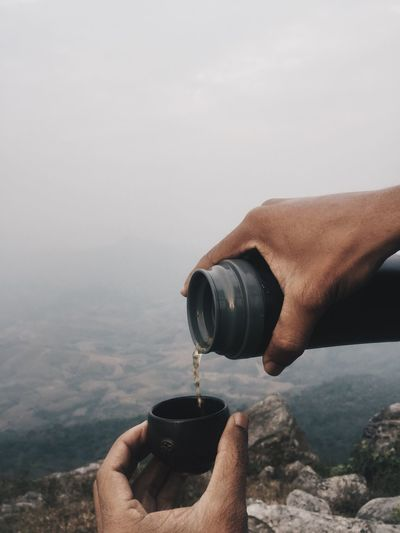 Cropped Hands Pouring Drink In Lid Against Landscape During Foggy Weather
