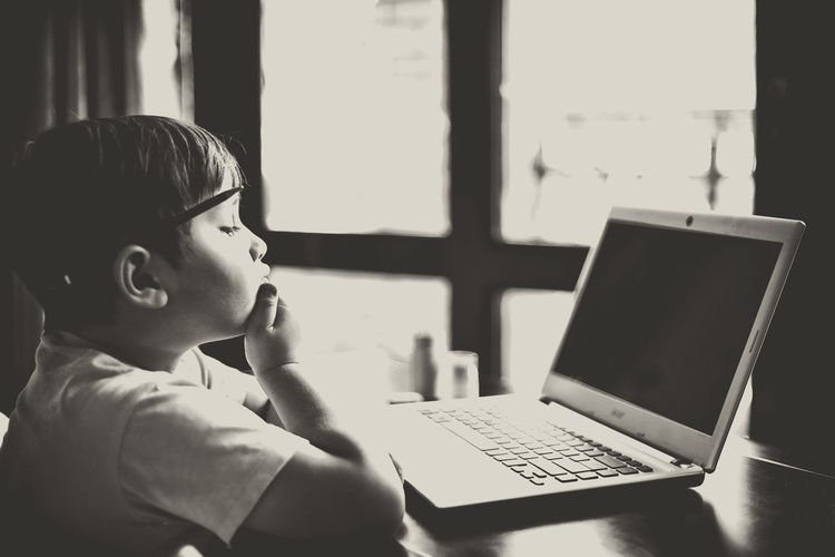 Young student sitting in front of a laptop, thinking Black And White Laptop Student Toddler  Young Boy Learning Homework Back To School Studying Thinker Thoughts Writting Inspirational Inspirations Inspired Think Thinking Black Screen Thoughtful My Year My View