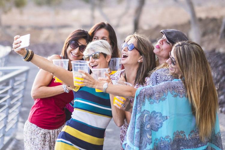 Friends enjoying drinks while taking selfie on beach