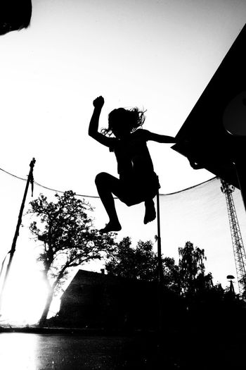 Low angle view of silhouette man jumping against sky