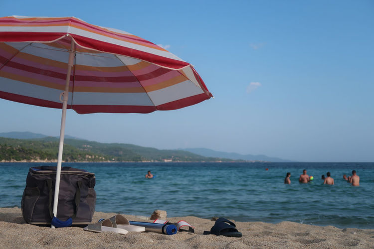 Umbrella on the beach Holiday Relaxing Travel Beach Clear Sky Flip-flop Holiday Leisure Activity Lifestyles Nature Outdoors Parasol People Real People Relax Scenics - Nature Sea Shade Sky Sunlight Sunshade Tourism Vacation Vacations Water