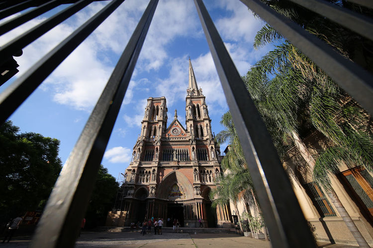 Low angle view of historic church seen through fence
