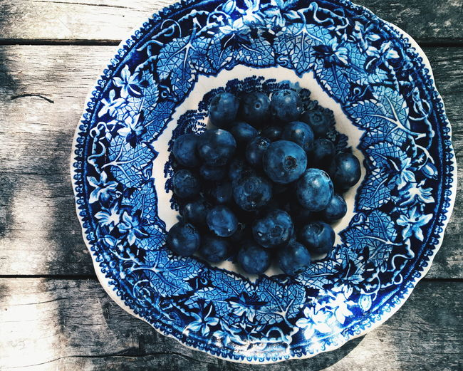 Directly above view of fresh blueberries in blue porcelain plate on table