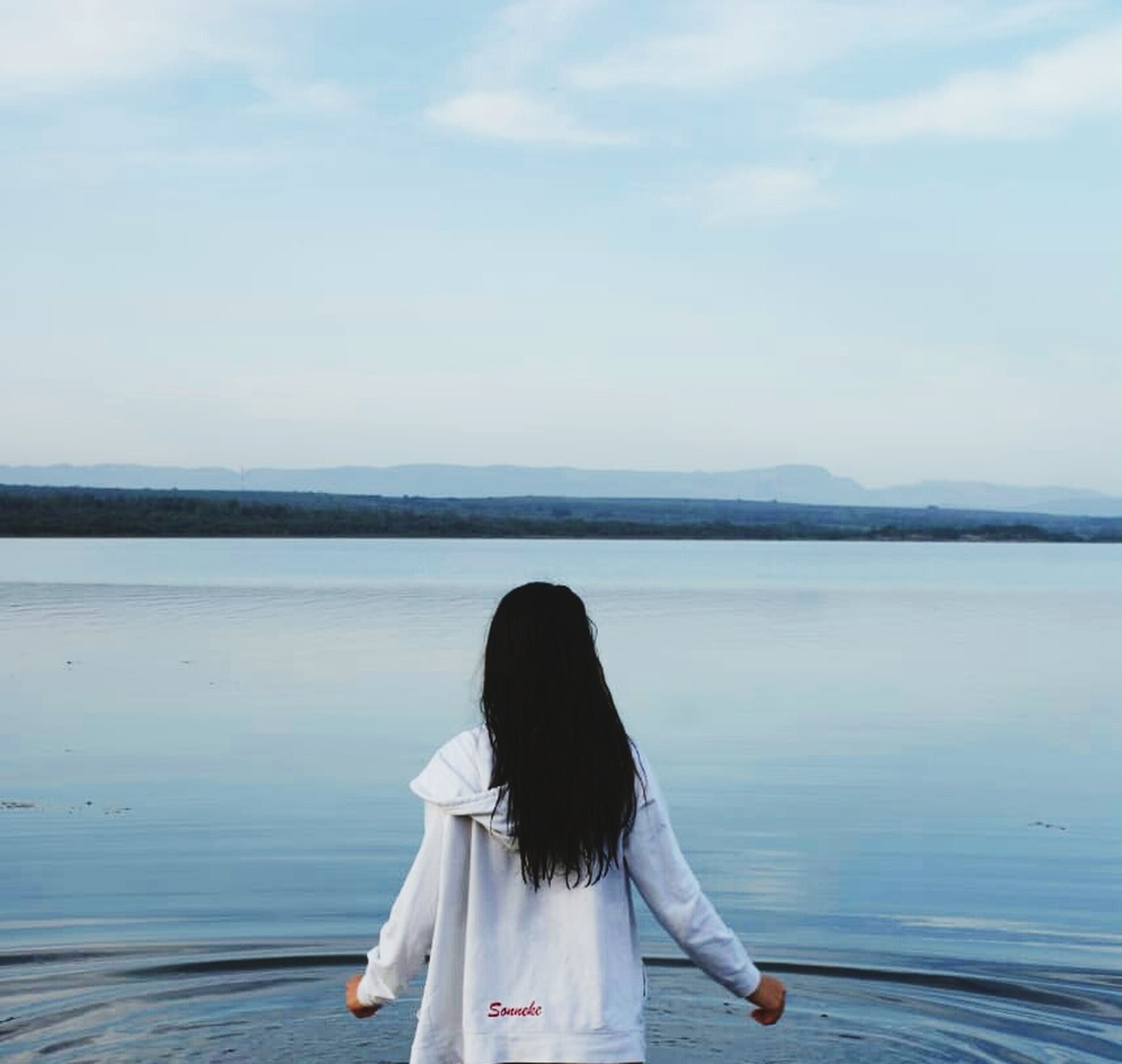 rear view, water, one person, real people, lifestyles, leisure activity, women, sky, beauty in nature, scenics - nature, adult, tranquil scene, day, hairstyle, standing, hair, long hair, nature, outdoors, looking at view