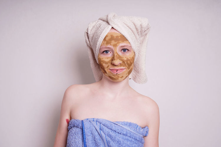 Portrait of young woman with facial mask wrapped in towel against white background