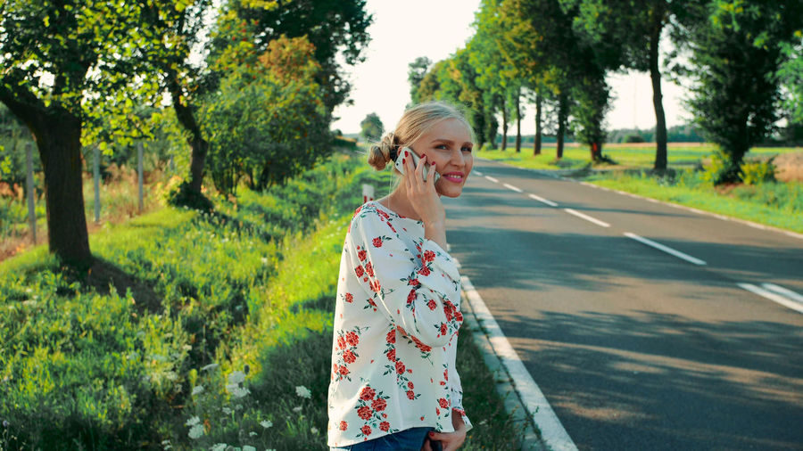 Young woman using phone while standing on road