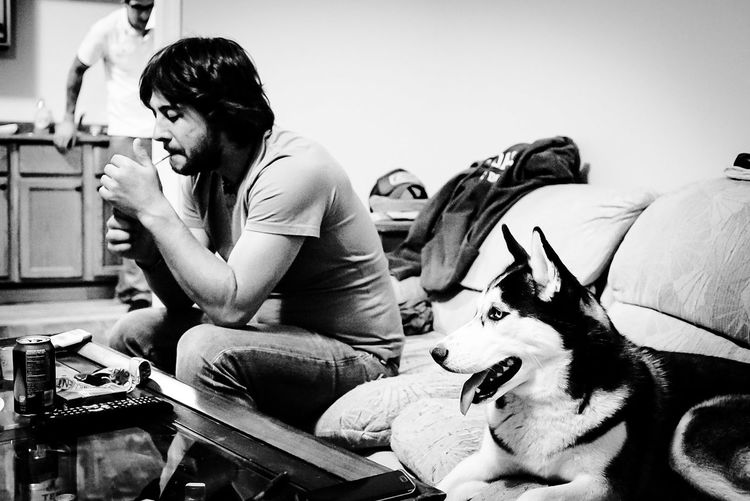 Man igniting cigarette sitting by malamute in living room at home