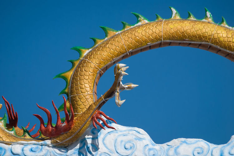 Low Angle View Of Chinese Dragon Statue Against Clear Sky