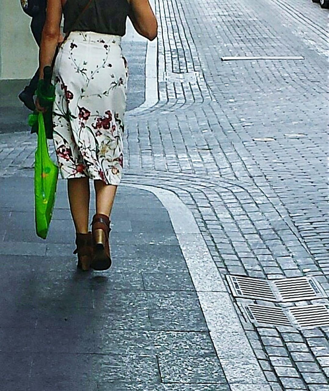 low section, walking, human leg, city street, human body part, street, outdoors, adult, one person, shorts, sidewalk, day, sandal, people, shoe, casual clothing, one woman only, adults only, only women, leg, city, standing, women, real people, young adult